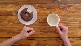 Manos del ` s de la mujer con el buñuelo del café y del chocolate metrajes