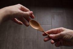 Manos del ` s de la mujer con la cuchara en fondo de madera oscuro Imágenes de archivo libres de regalías