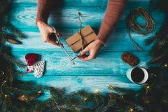 Manos del ` s de la mujer que envuelven el regalo de la Navidad Foto de archivo