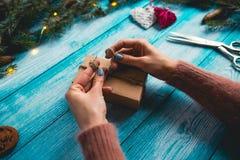 Manos del ` s de la mujer que envuelven el regalo de la Navidad Imagen de archivo