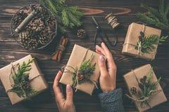 Manos del ` s de la mujer que sostienen los regalos de la Navidad o del Año Nuevo envueltos en kra Foto de archivo
