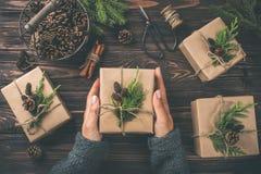 Manos del ` s de la mujer que sostienen los regalos de la Navidad o del Año Nuevo envueltos en kra Foto de archivo libre de regalías