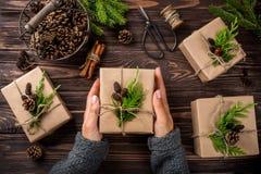 Manos del ` s de la mujer que sostienen los regalos de la Navidad o del Año Nuevo envueltos en kra Fotografía de archivo libre de regalías