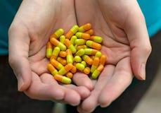 Manos del ` s de la mujer que sostienen muchas píldoras Imagen de archivo