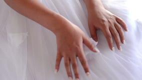 Manos del ` s de la novia con la manicura en el vestido de boda almacen de video