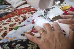 Manos del ` s de la señora que hacen un edredón imagen de archivo