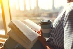 Manos del ` s de las mujeres con café y un libro por la ventana fotografía de archivo libre de regalías