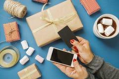 Manos del ` s de las mujeres con la tarjeta de crédito y la melcocha del cacao de los regalos del teléfono Imágenes de archivo libres de regalías
