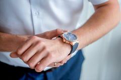 Manos del ` s de los hombres con un reloj Fotos de archivo