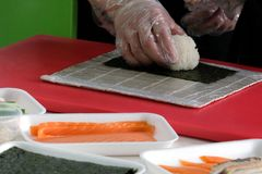 Manos del ` s de los hombres en los guantes transparentes, arroz puesto en una hoja del nori para cocinar el sushi y los rollos I Imagen de archivo