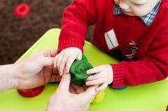 Manos del ` s de los niños con los adultos que sostienen la arcilla verde Fotografía de archivo