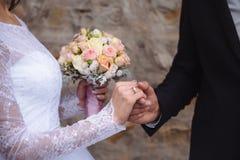Manos del ` s de novia y del novio con los anillos de bodas en la tabla marrón Imagen de archivo