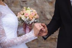 Manos del ` s de novia y del novio con los anillos de bodas en la tabla marrón Fotografía de archivo
