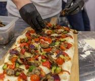 Manos del ` s del cocinero que preparan la pizza grande imagenes de archivo