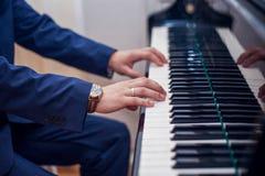 Manos del ` s del hombre en el piano Imagen de archivo