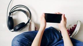 Manos del ` s del niño con el smartphone y los auriculares Imagenes de archivo