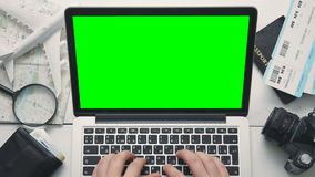 Manos del ` s del viajero de la visión superior usando el ordenador portátil con la pantalla verde en el escritorio de madera bla almacen de video