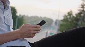 Manos del ` s del hombre joven usando un móvil al aire libre almacen de video
