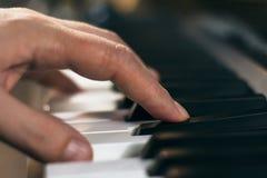 Manos del ` s del hombre que juegan el piano Foto de archivo