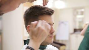 Manos del ` s del peluquero en el proceso de trabajo Peluquero que hace corte de pelo de hombre atractivo en salón de la belleza  metrajes
