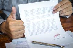 Manos del sello del hombre de negocios en el documento de papel para aprobar el acuerdo de contrato de la inversi?n empresarial foto de archivo libre de regalías