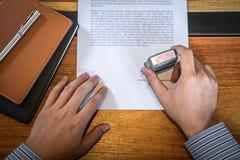 Manos del sello del hombre de negocios en el documento de papel para aprobar el acuerdo de contrato de la inversi?n empresarial imagen de archivo libre de regalías