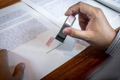 Manos del sello del hombre de negocios en el documento de papel para aprobar el acuerdo de contrato de la inversi?n empresarial imagenes de archivo