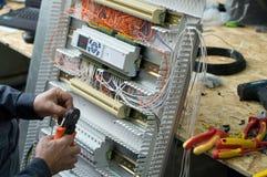 Manos del técnico eléctrico que montan el cubículo de control industrial de la HVAC de la baja tensión en taller Foto del primer fotos de archivo