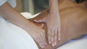 Manos del terapist que dan masajes detrás de cliente femenino adulto en clínica del balneario almacen de metraje de vídeo
