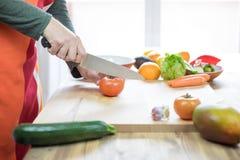 Manos del tomate del corte del hombre en tabla de cortar de madera Foto de archivo libre de regalías