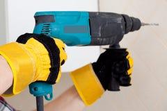 Manos del trabajador con el perforador Fotografía de archivo libre de regalías