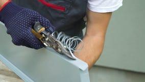 Manos del trabajador en los guantes protectores que preparan el metal del corte del travesaño de la ventana del PVC con el primer almacen de video