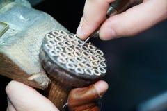 Manos del trabajador que trabajan con los marcos para las joyas foto de archivo libre de regalías