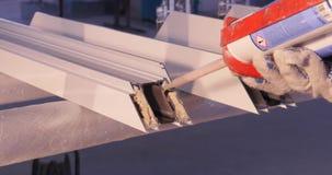 Manos del trabajador que usa un tubo del silicón para reparar de la ventana interior Detalles de la ventana del aluminio Trabajad almacen de metraje de vídeo