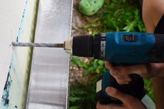 Manos del trabajador usando el taladro eléctrico fotografía de archivo