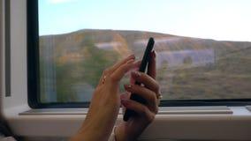 Manos del ` un s de la señora joven usando Smartphone en el tren Fotografía de archivo