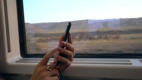 Manos del ` un s de la señora joven usando Smartphone en el tren Imágenes de archivo libres de regalías