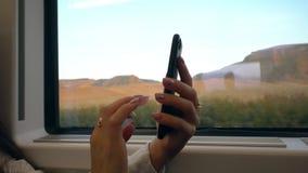 Manos del ` un s de la señora joven usando Smartphone en el tren Fotografía de archivo libre de regalías