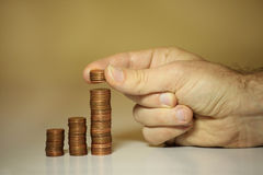 Manos del varón que empilan centavos y peniques Imagen de archivo