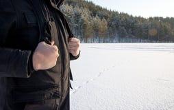 Manos del viajero del viajero que celebran una correa de la mochila en el fondo de un llano nevoso El ir de excursión Viaje fotografía de archivo