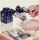 Manos del viejo hombre, fotos con la lupa a partir del pasado, cámaras retras de la visión en la tabla, filtrada Imagen de archivo libre de regalías