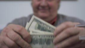 Manos del viejo hombre que cuenta dólares cerca para arriba El hombre rico positivo demuestra su dinero Ocio de próspero jubilado almacen de video