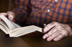 Manos del viejo hombre que sostienen un libro Foto de archivo libre de regalías