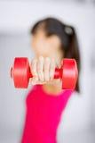 Manos deportivas de la mujer con pesas de gimnasia rojas claras Imagenes de archivo
