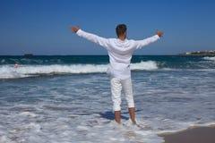 Manos derechas de un hombre joven extendidas en la costa Foto de archivo libre de regalías