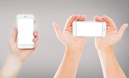 Manos determinadas que sostienen los teléfonos móviles vacíos de la pantalla en blanco en la exhibición vacía gris del fondo, ver fotos de archivo