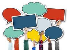 Manos diversas que llevan a cabo burbujas coloridas del discurso Imagen de archivo libre de regalías