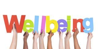 Manos diversas que llevan a cabo el bienestar de la palabra Foto de archivo