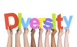 Manos diversas que llevan a cabo la diversidad de la palabra Fotos de archivo libres de regalías