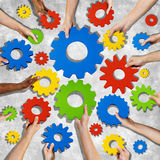 Manos diversas que sostienen los engranajes coloridos Fotografía de archivo libre de regalías